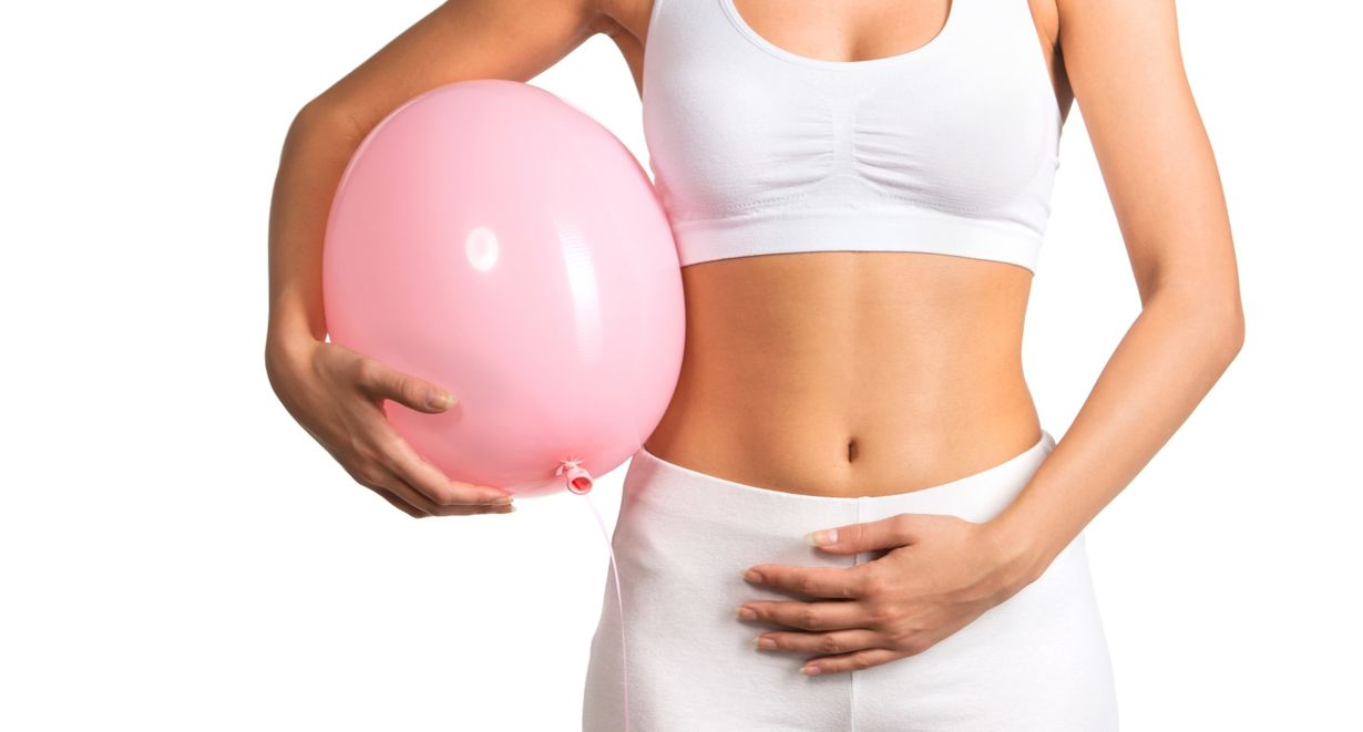 Picture of a slim lady holding on to a balloon beside her tummy