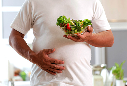 Picture of a man suffering from bloated stomach holding on to a bowl of healthy salad