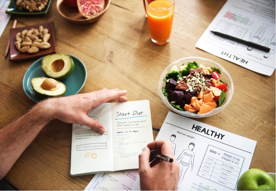 Picture of a man having a diet plan with healthy food placed around him