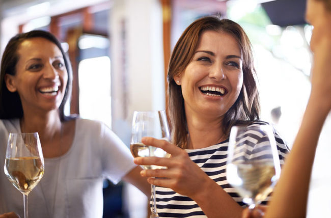 Picture of a few happy ladies holding on to a glass of champagne