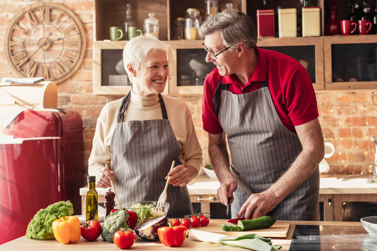 A picture of a pair of elderly couple preparing food
