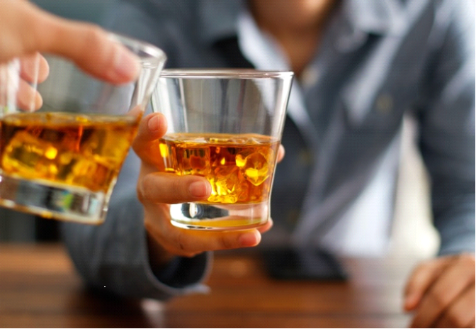 2 people holding on to a cup of whiskey raising a toast