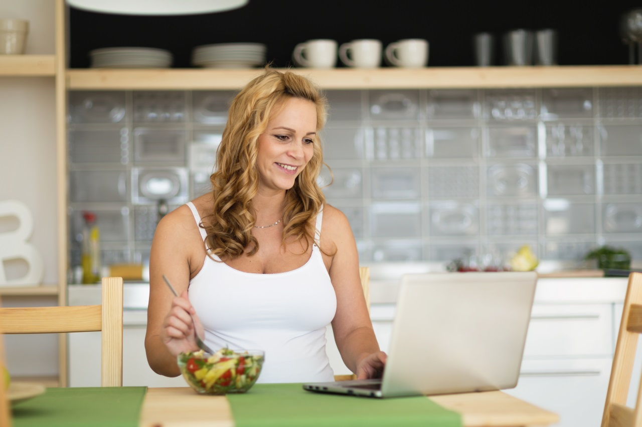 A happy lady having her healthy bowl of salad infront of her laptop
