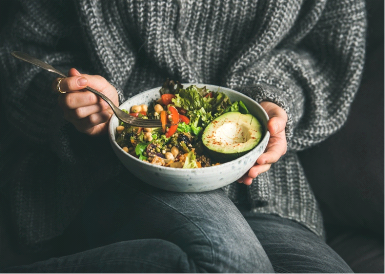 A picture of a lady having healthy bowl of salad