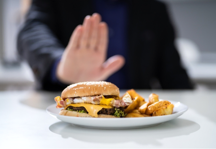 A picture of a lady rejected a plate of burger and fries