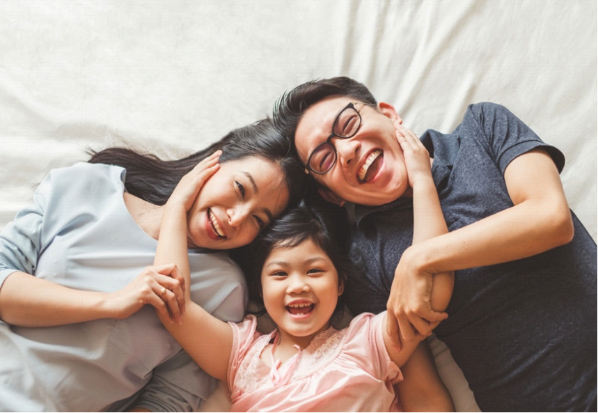 Picture of a happy family lying down on bed