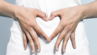 Picture with a lady doing a heart sign gesture near her tummy